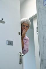 ängstliche Seniorin öffnet die Tür