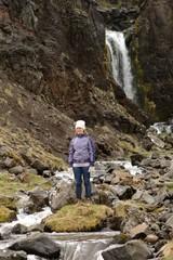 Frau steht vor einem natürlichen Wasserfall in Island