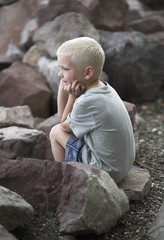 Little boy sits on rough rocks