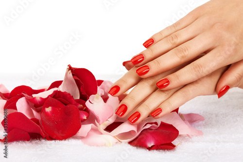 Closeup image of red manicure with leafs of rose