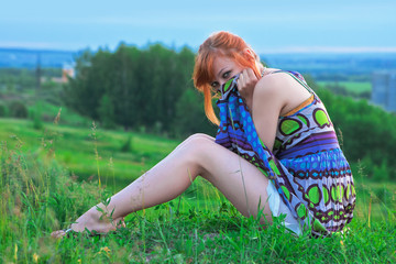 Beautiful ginger-haired woman sitting on the ground