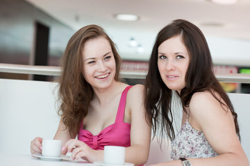 Two girls sitting in cafe in shopping center
