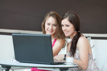 Two girls work on a laptop, sitting in cafe in shopping center
