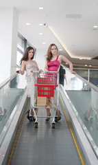 Two friends with purchases on the escalator