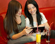 Girls in cafe using modern tablet PC