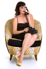 Brunette sitting and talking on a old phone in yellow shoes