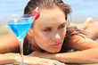 young woman on the beach with cocktail