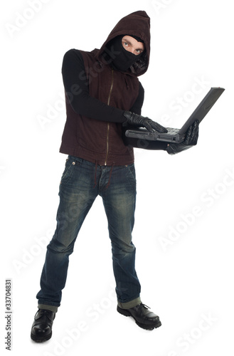 computer hacker - criminal in balaclava with the laptop