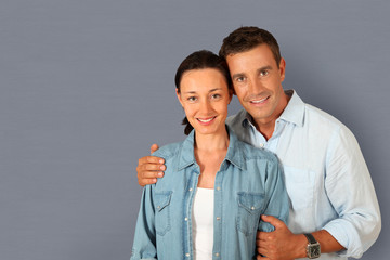 Portrait of couple standing on grey background