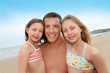 Portrait of father with daughters at the beach