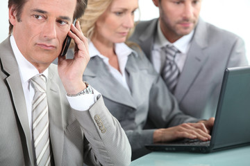 Man on cellphone whilst colleagues use laptop