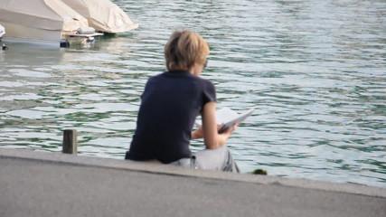 Frau liest ein Buch am See