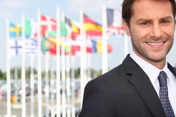 Smiling male executive in front of various flags