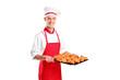 A male baker holding freshly baked croissants