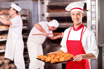 Male baker holding freshly baked croissants in bakery