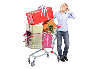 A woman posing next to a shopping cart full with gifts