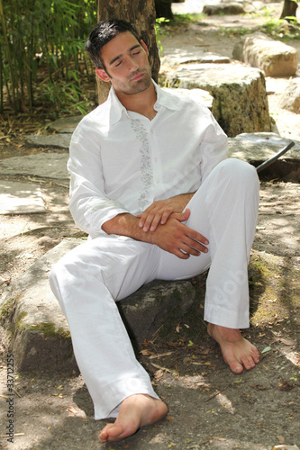 30 years old man sleeping and leaning against a tree