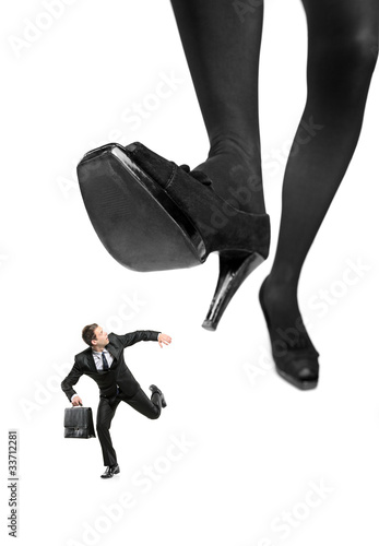 Afraid businessman running away from a big foot