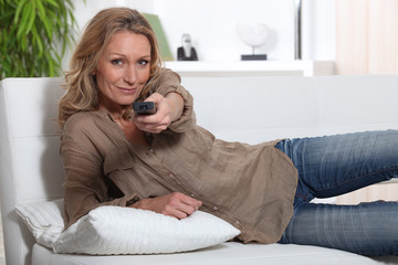 Woman laid on couch holding television remote control