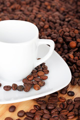 White cup with saucer on coffee beans