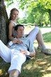 Portrait of sporty couple relaxing by tree