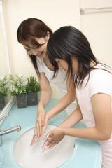 手を洗う母親と娘