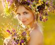 Portrait of Young beautiful woman wearing a wreath of wild flowe