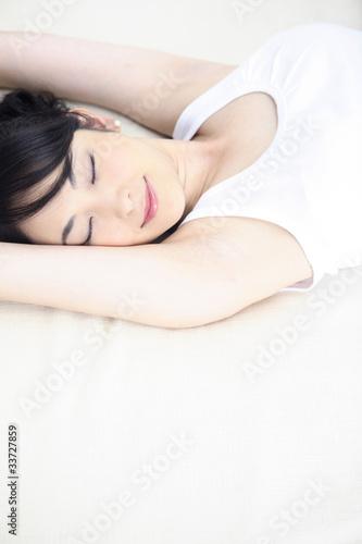 ベッドで昼寝する女性