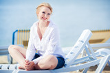 Beautiful woman sitting in chaise on the beach