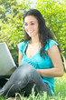 happy young woman using laptop outdoors