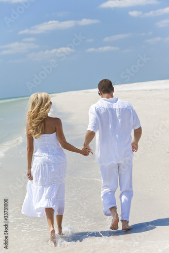 Happy Young Couple Running or Walking Holding Hands on Beach