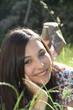 junge Frau mit braunem Haar liegt auf der Wiese im Garten