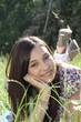 junge Frau liegt auf der Wiese zwischen Blumen und entspannt