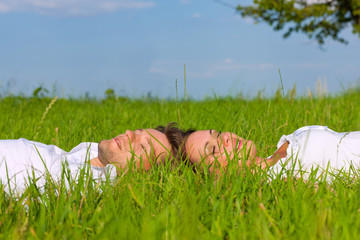Happy couple lying on a meadow dreaming