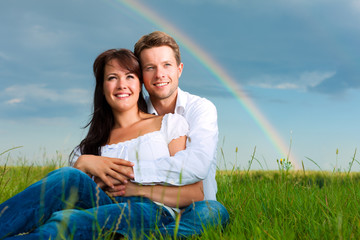 Happy couple sitting on a meadow under rainbow
