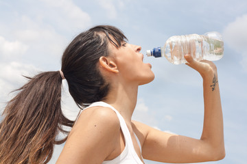 Healthy woman drinking water during exercise