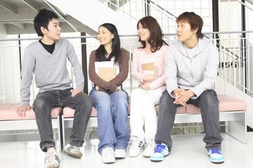 ベンチに座って話す大学生達