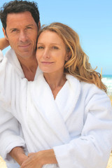 Man and woman in toweling robes on the beach
