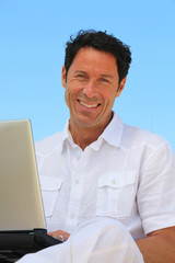 Man smiling on laptop in blue sky