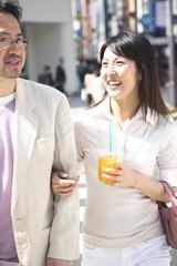 飲み物を飲みながら街を歩くミドルカップル