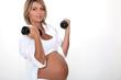 Pregnant woman lifting handweights