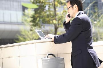 携帯電話で話すビジネスマン