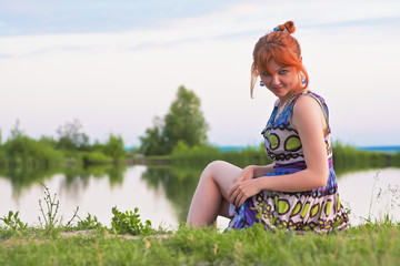 Beautiful ginger-haired woman at the coast of pond
