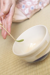 抹茶を茶碗に入れる女性の手元
