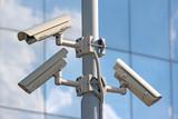 three security cctv cameras on the light pylon poster
