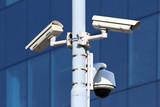 three security cctv cameras on the public light pylon poster
