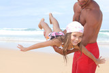 Man flying his daughter around a beach