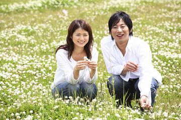 公園で白つめ草を摘むカップル