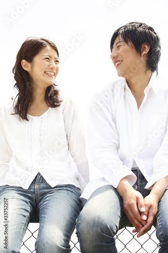 フェンスの上に座るカップル