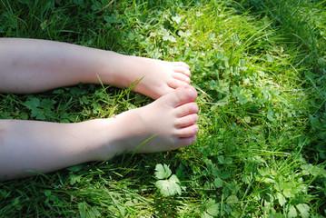 Wiese im Schatten und Kinderbeinen